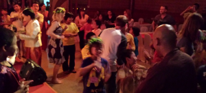 The riders, children, and staff enjoying a dance after the dinner at the end of the ride – Christina still wearing the garland given to her by the children.
